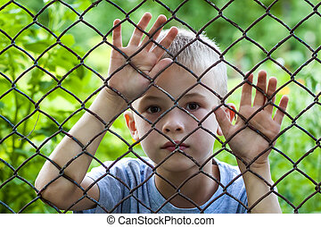 Portrait of a little boy behind chain link fence