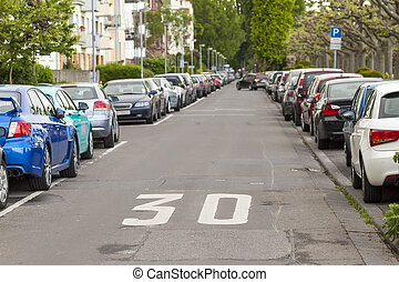 Rows of cars parked on the roadside in residential district