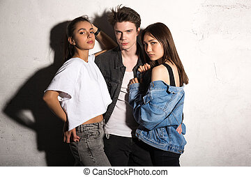 Concentrated young hipster man standing with friends women