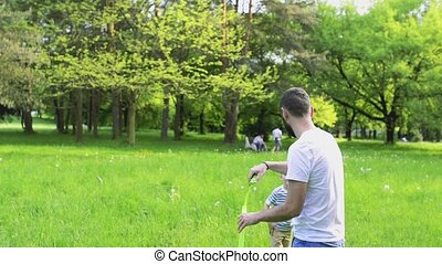 Hipster father and son blowing bubbles outdoors in park. -...
