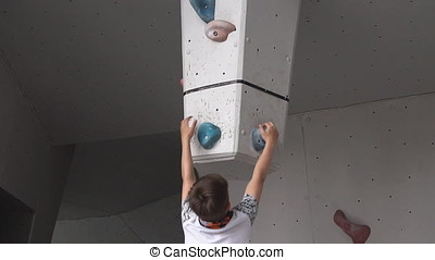 Boy climbs on a rock on the climbing wall. young athletic...