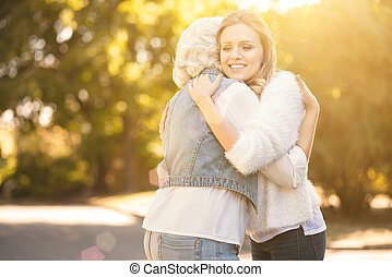 Positive young woman hugging pensioner outdoors - Full of...
