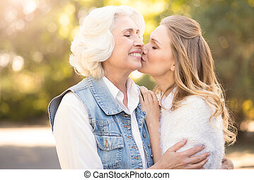 Involved woman kissing elderly mother in the park -...