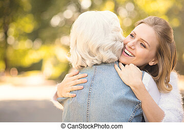 Smiling young woman hugging old mother in the park - Love...
