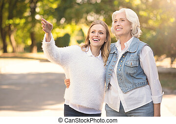 Happy aging woman and mature daughter walking in the park -...