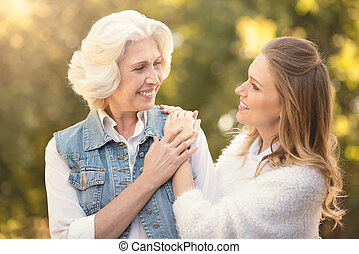 Young woman enjoying sunny weather with aged mother in the...