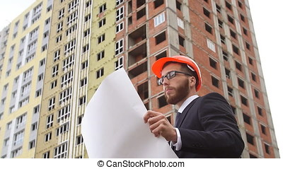 Architect looking at building plans with new construction. Slow motion