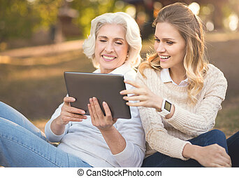 Modern woman spending picnic with old mother in the park -...