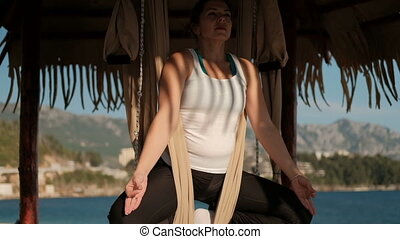 Sport woman doing yoga Sits in lotus pose, hanging on cloth...