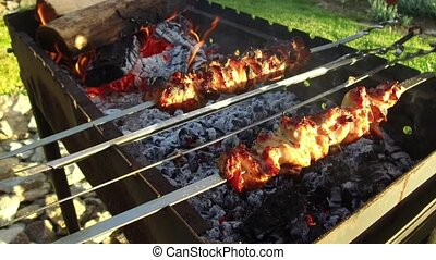 hand turning skewers with meat on brazier outdoors -...