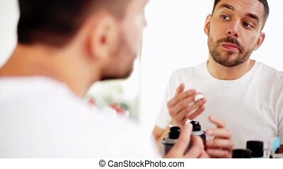 man applying shaving foam to beard at bathroom - beauty,...