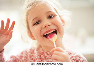 Portrait of happy child girl with lolipop in her hand -...