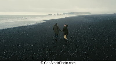 Back aerial view of the young couple walking on the black volcanic beach in Iceland. Romantic date near the sea.