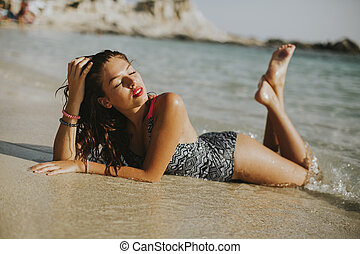 Pretty young woman lying on the beach