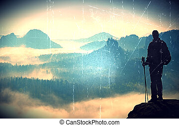 Film grain. Silhouette of tourist with poles in hand. Sunny...
