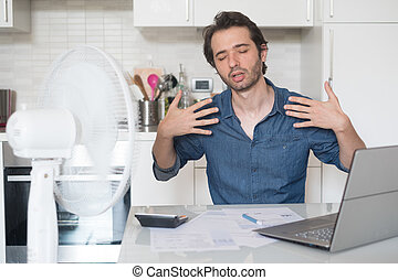 Sweaty man trying to refresh from heat with fan - Sweaty man...