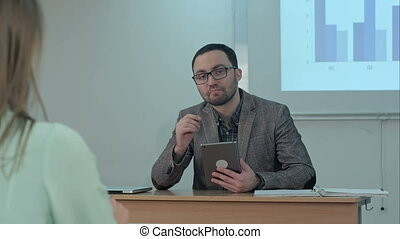 Male teacher holding digital tablet sitting in front of students and talk to a camera