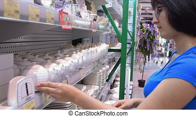 Woman choosing dishware in the store - Young woman looking...