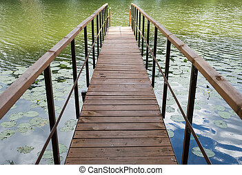 wooden gangway on the lake - wooden gangway with railings on...