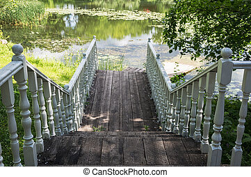 wooden gangway on the lake - White wooden gangway with...