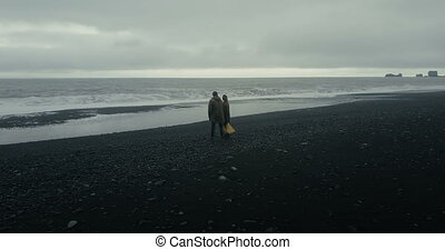 Aerial view of young couple standing on black volcanic beach...