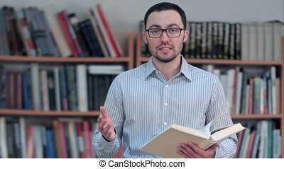 Positive teacher or tutor talking ta a camera , holding a book in his hands