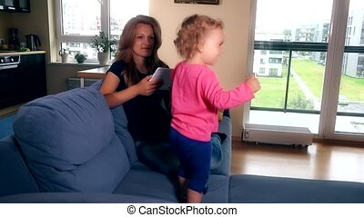 Happy mother with little child girl have fun listening music on tablet computer