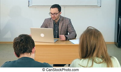 Young teacher sitting in school classroom with laptop,...