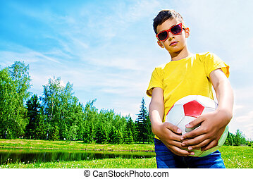 football on a lawn - Happy boy plays football in the park....