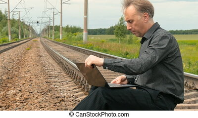 A man is sitting on the rails and working on a laptop....