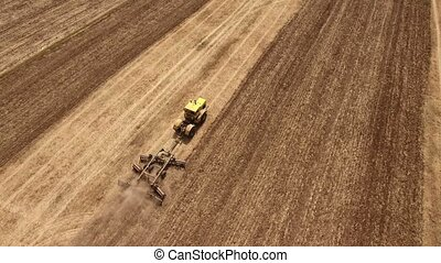 Aerial shot of a wheat field and a powerful tractor pulling...