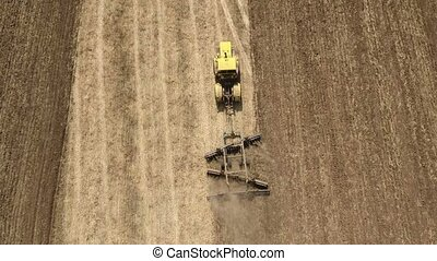 Aerial shot of a boundless wheat field and a tractor pulling a harrow in summer