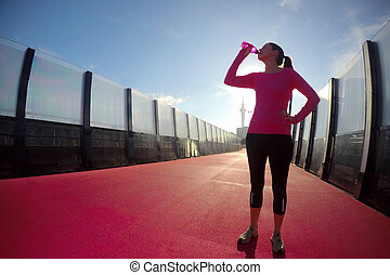 Young woman drinking water on a bright pink road - Young...