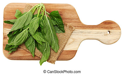 Yu Choy Leaves - Yu Choy Leaf bundle on cutting board.