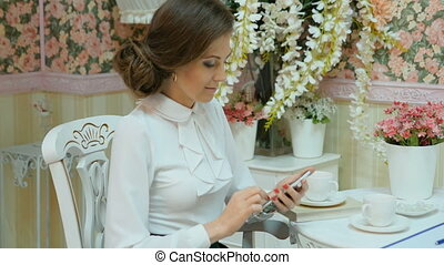 Young beautiful businesswoman in white clothes. Dials SMS on...