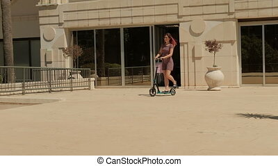 Young woman rides scooter in summer day outdoors. She moves...