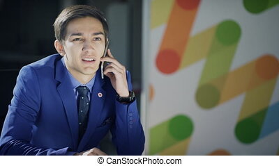 A man in a business suit is talking on the phone reluctantly.