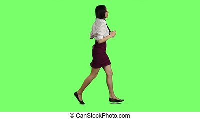 Girl of Asian appearance with a phone is running to an important meeting. Green screen. Slow motion