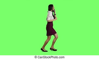 Girl with a phone is running to an important meeting. Green screen. Slow motion