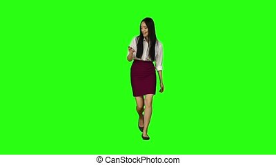 Girl of asian appearance walks the street, the phone looks at interesting pictures. Green screen. Slow motion