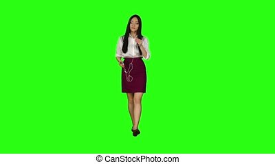 Asian girl goes to work and listens to music in headphones. Green screen. Slow motion