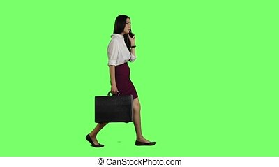 Girl speaks on the phone, in the hand holds a diplomat. Green screen. Slow motion