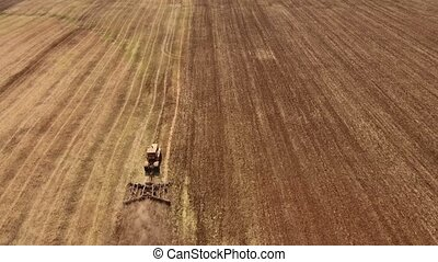 Aerial shot of a wheat field and a tractor pulling a disc...