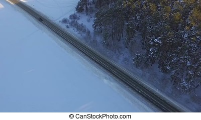 One car driving through the winter forest on country road. Top view from drone. Aerial view of a road through the forest high up in the mountains in the winter with snow covered trees