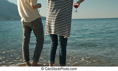 Man and woman standing on beach with glasses red wine in...