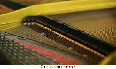 Close up of inside retro piano's hammers striking strings