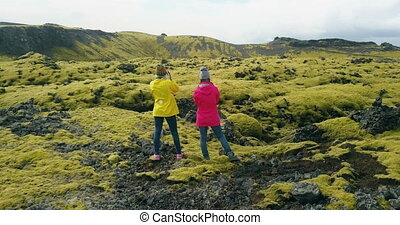 Aerial view of two woman standing on the lava field in Iceland and enjoying the landscape. Tourists after hiking.