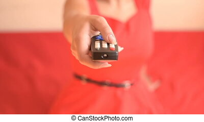 TV remote control in hand - Woman switches TV channels Woman...