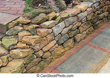 Dry wall without mortar. - Wall of natural sandstone roughly...