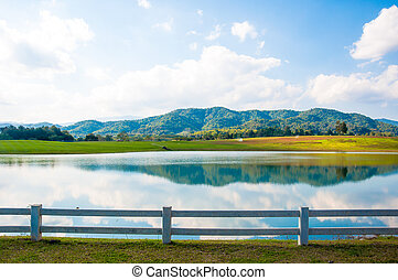 the lake and mountain with white hedge fence on blue sky background